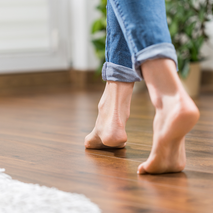 Barefeet walking on wooden floor
