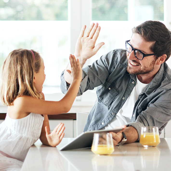 Father and daughter at kitchen table high five for free gas connection