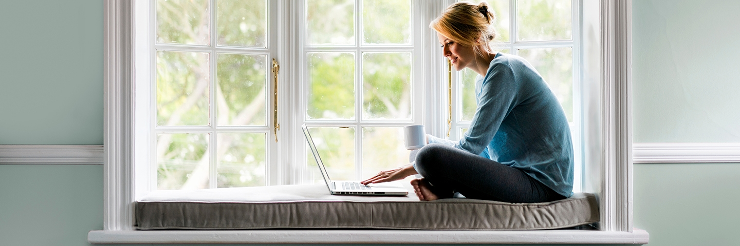 Woman in bay window looking at thegashub.co.nz on laptop