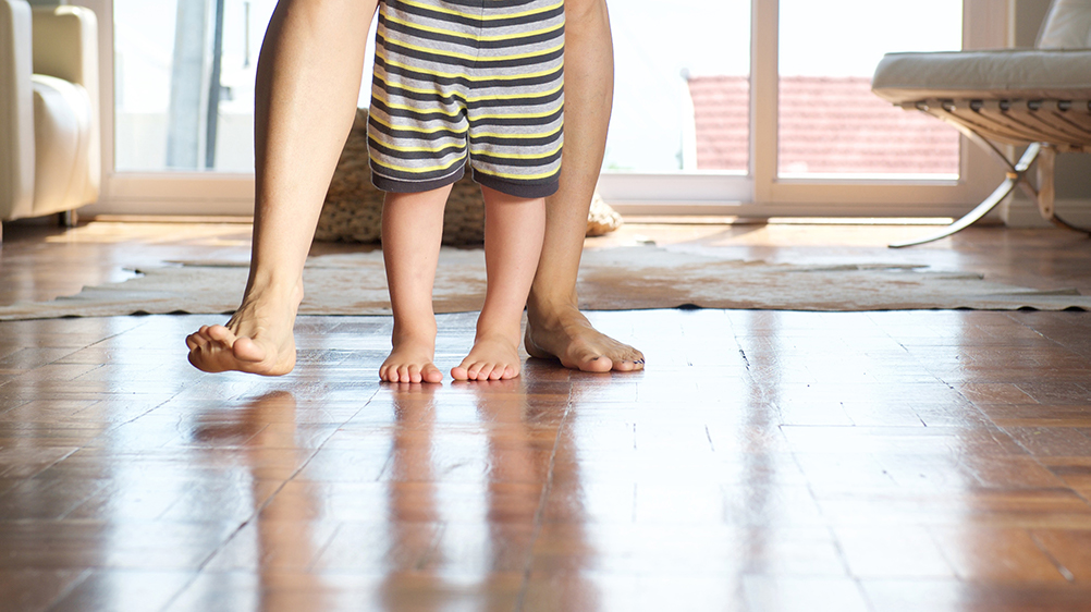 Parent and child in barefeet on wooden floor