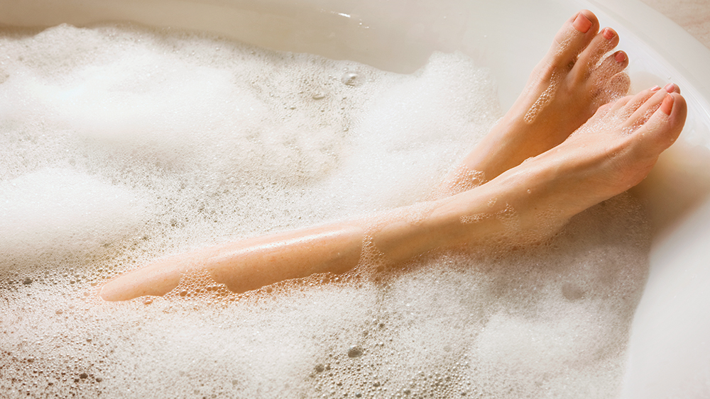 Women's feet in bubble bath powered by natural gas hot water