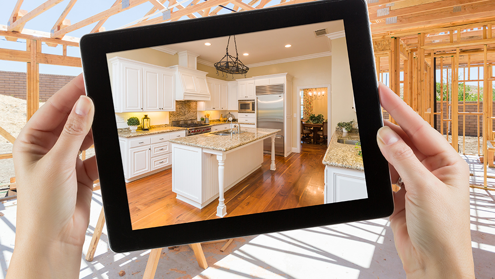 Hands holding iPad showing renovated kitchen