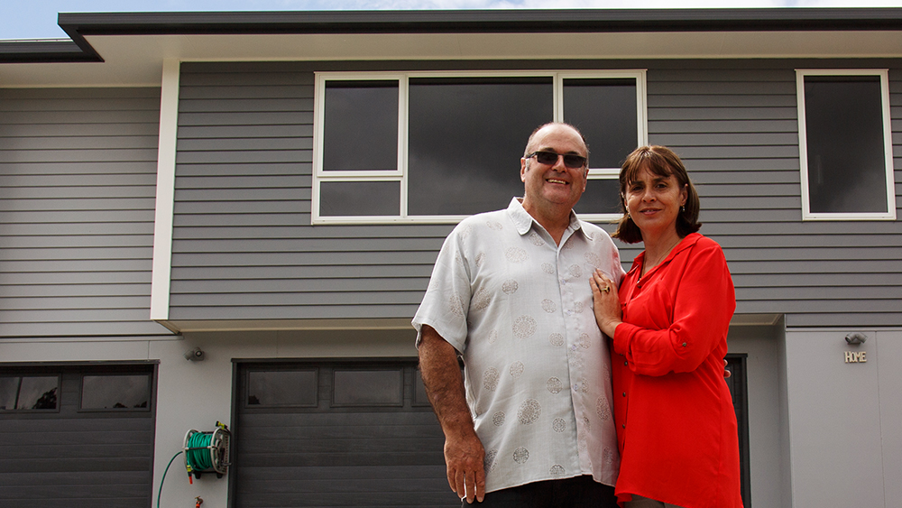 The OKanes in front of their rebuilt home powered by gas