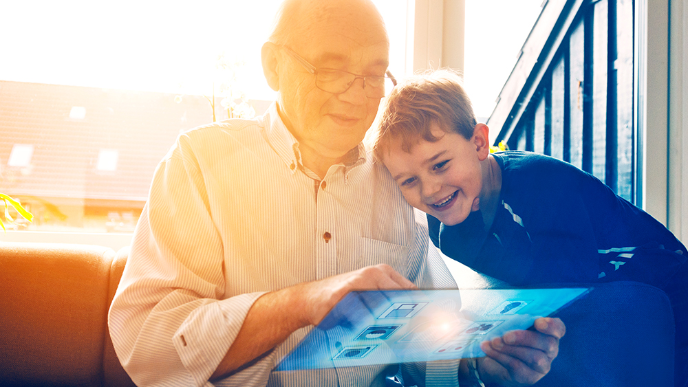 Grandfather and grandson on futuristic smart home device