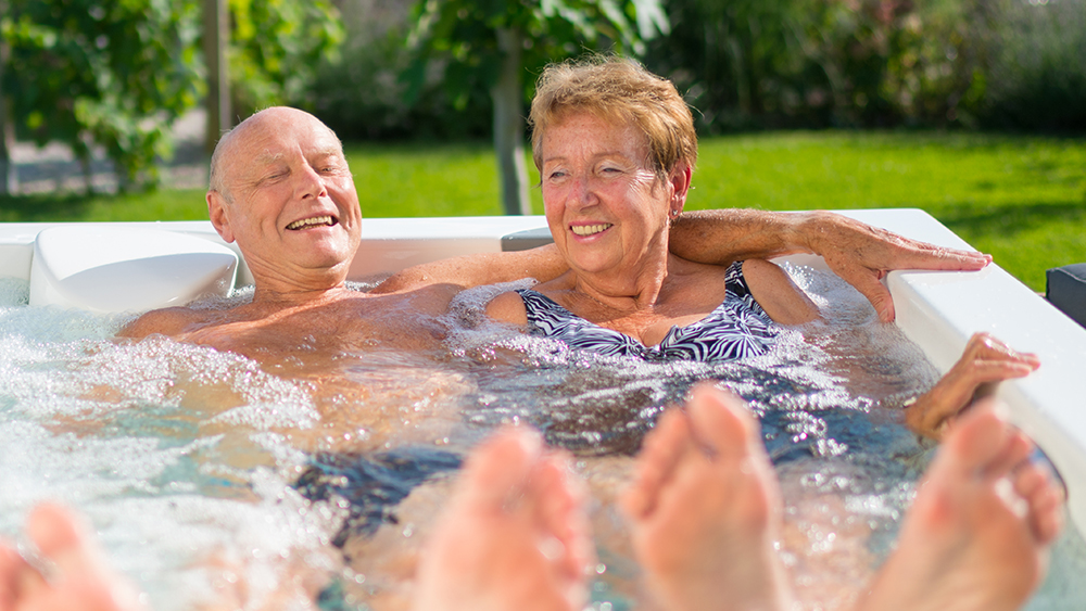 Older couple with feet up in spa pool