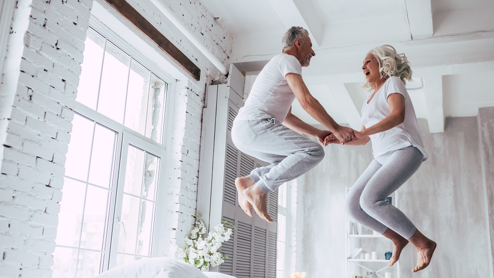 Older couple jumping on bed excitedly for free connection
